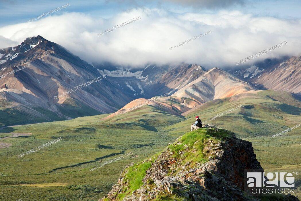 Stock Photo: Senior man sits on a rock outcrop at Polychrome Pass with Alaska Range in the background, Denali National Park & Preserve, Interior Alaska, summer.