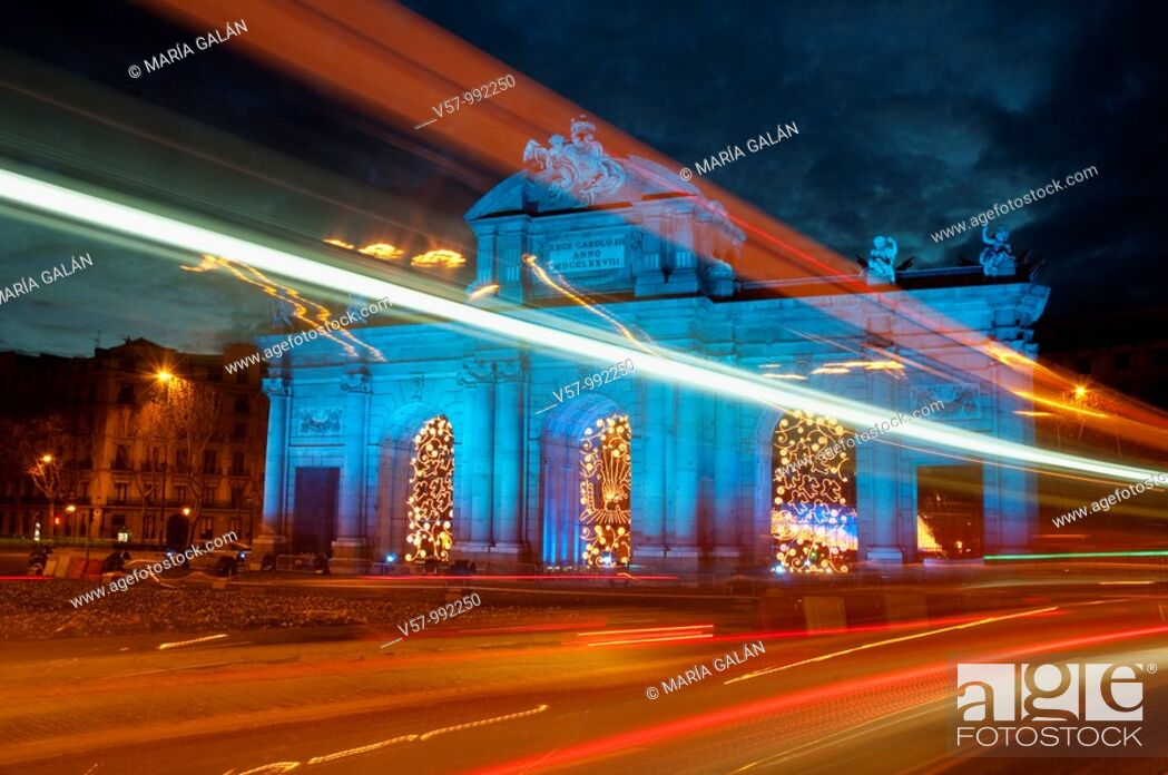 Stock Photo: Puerta de Alcalá illuminated in blue and light trail, commemorating the Spanish presidency of European Union, night view. Madrid, Spain.