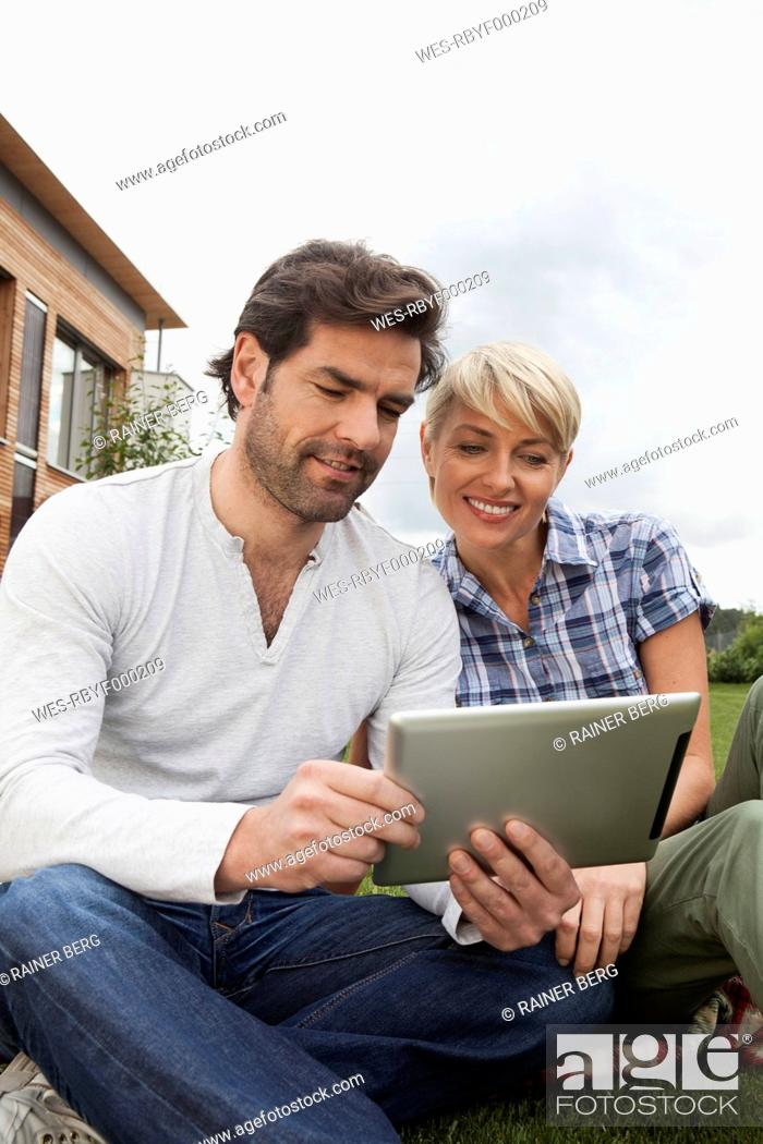 Stock Photo: Germany, Bavaria, Nuremberg, Mature couple using digital tablet in garden.
