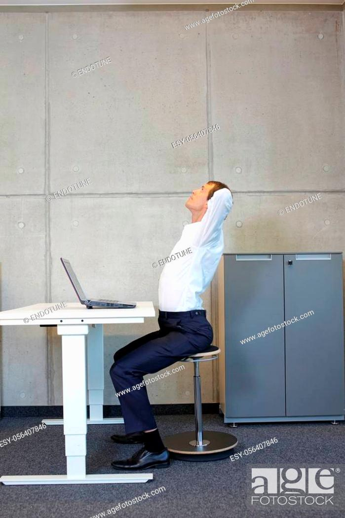 Stock Photo: Business man exercising on pneumatic leaning seat with laptop at electric height adjustable desk in office - stretching at desk.