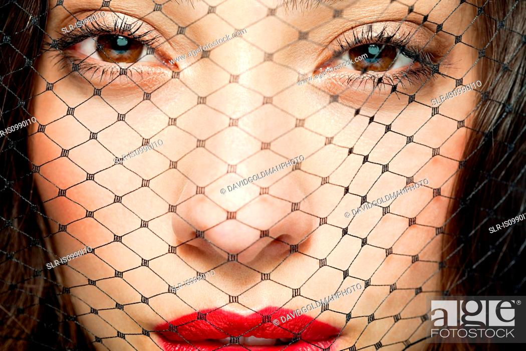 Stock Photo: Woman with netting covering face.