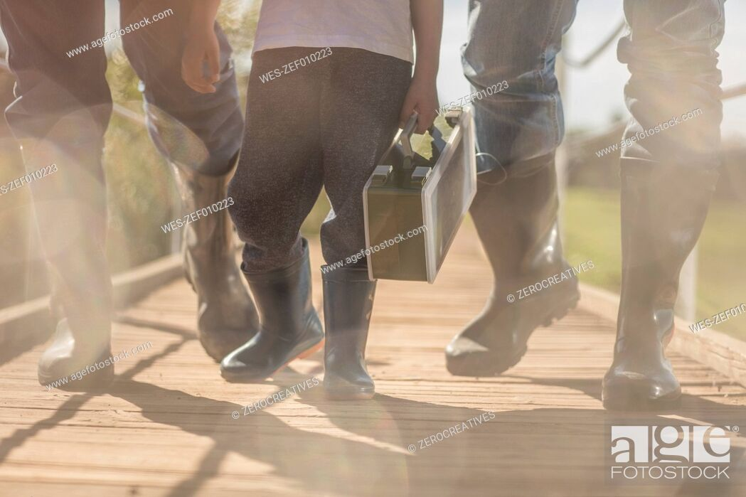 Stock Photo: Two men and little boy wearing gumboots walking over bridge with box.