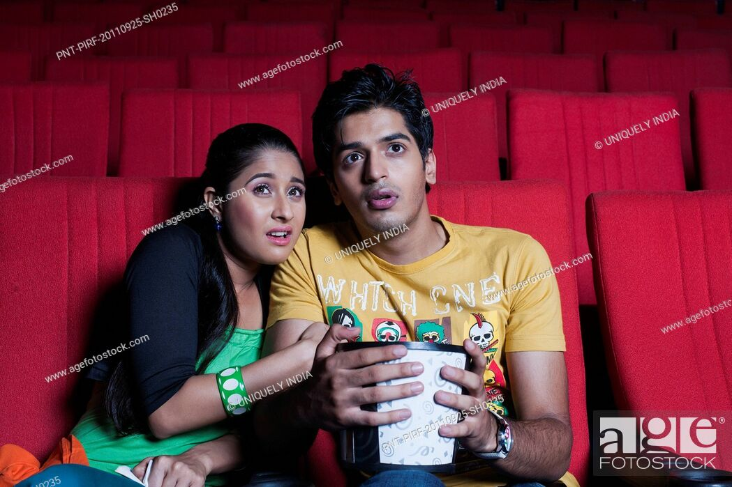 Stock Photo: Couple watching a horror movie in a cinema hall.