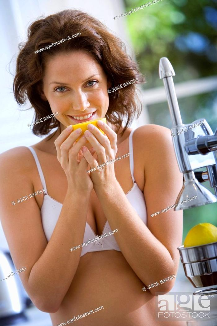 Stock Photo: Young woman in underwear with orange by juicer, smiling, portrait.