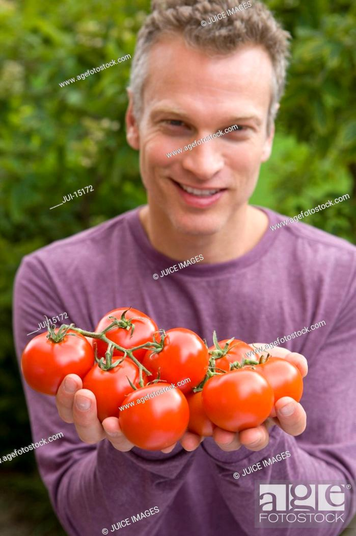 Stock Photo: Man with handful of tomatoes, portrait.