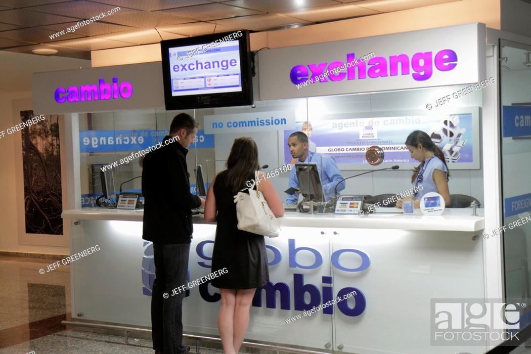 Stock Photo: Dominican Republic, Santo Domingo, Las Américas International Airport, SDQ, exchange bank, counter, agent, money, currency, Hispanic, man, woman, couple, booth.