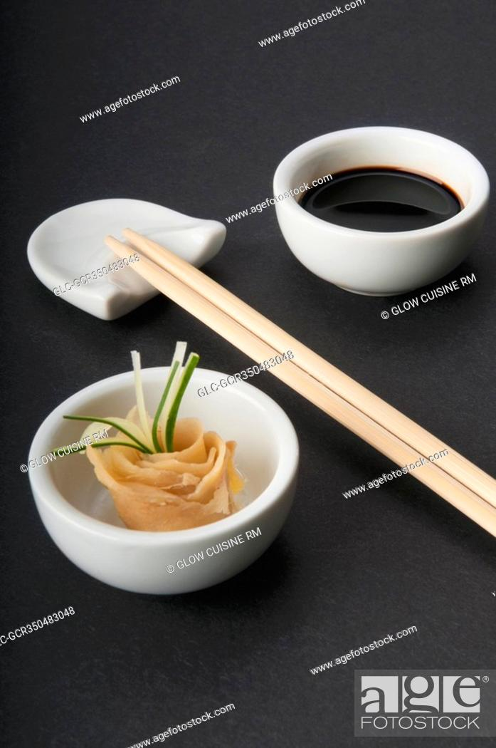 Stock Photo: Close-up of chopsticks with soy sauce and pickled ginger.