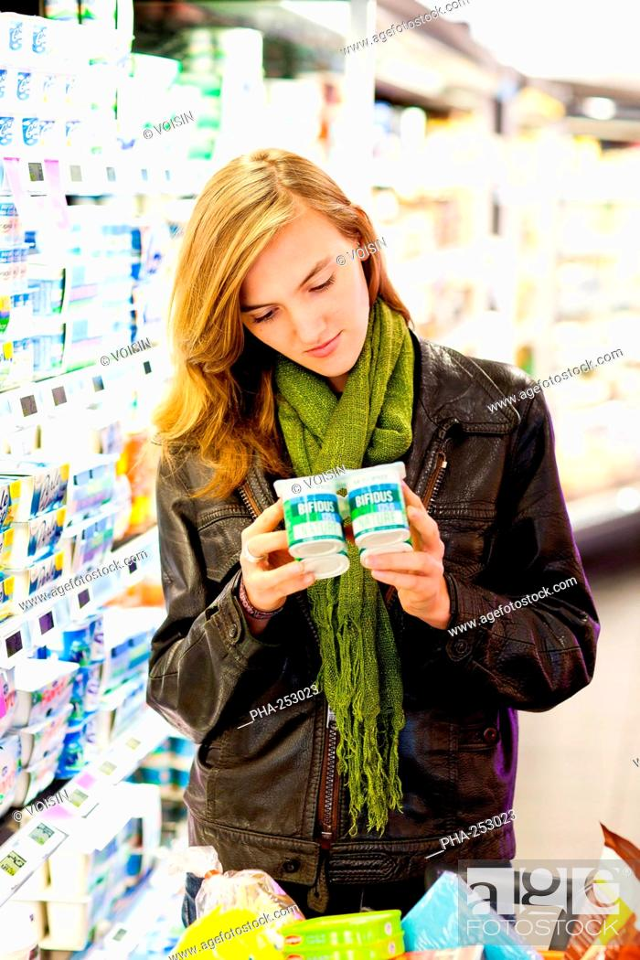 Stock Photo: Woman shopping for dairy products in supermarket.
