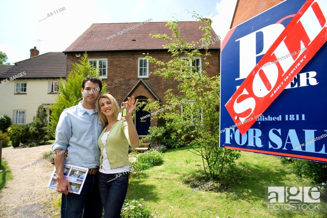 Stock Photo: Couple arm and arm outside house by 'sold' sign, portrait.