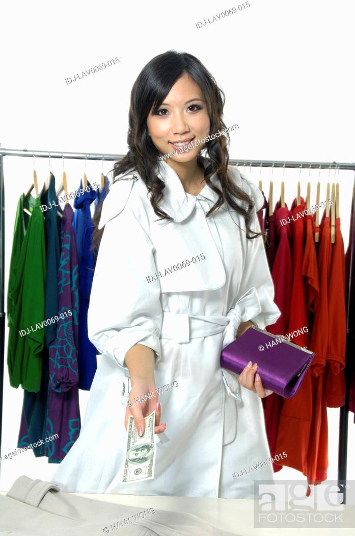 Stock Photo: Woman holding paper currency and purse in a clothing store.