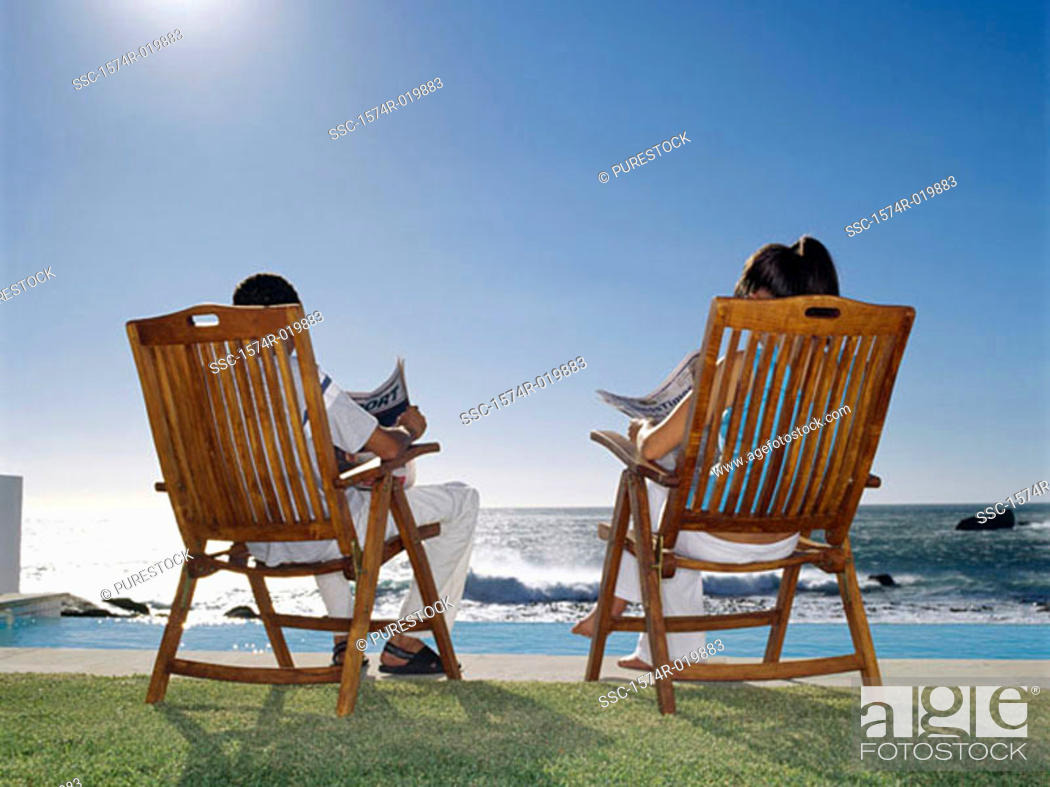 Stock Photo: Rear view of a young couple sitting on chairs at the poolside.