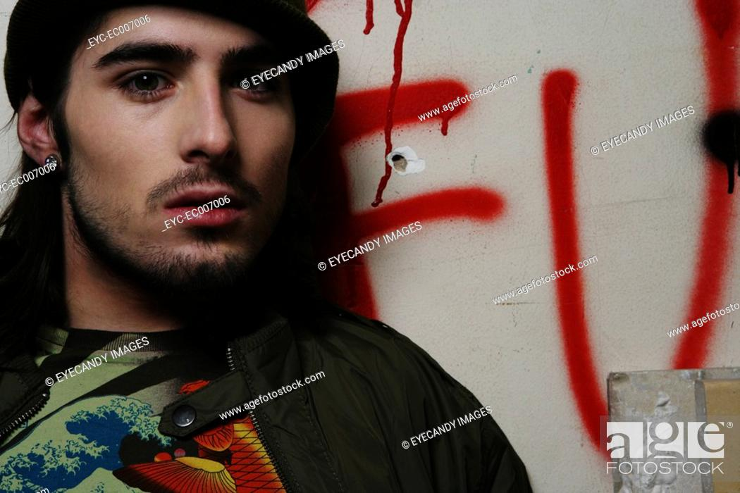 Stock Photo: Young man against a graffiti wall.