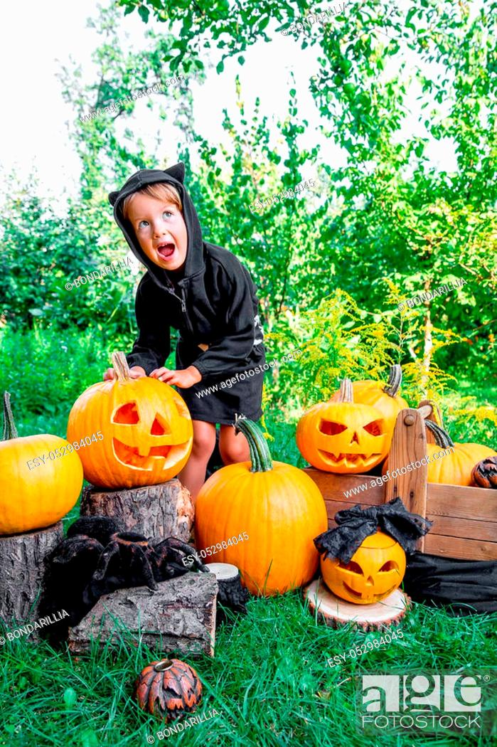 Stock Photo: Halloween. Child dressed in black with jack-o-lantern in hand, trick or treat. Scaring little girl with pumpkin in the wood, outdoors.