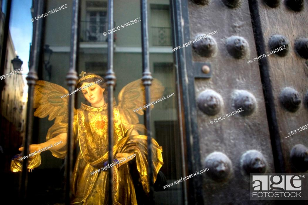 Stock Photo: A statue of Saint Raphael Arcangel sits behind a window as the city of Cadiz is reflected in Andalusia, Spain, April 17, 2010.
