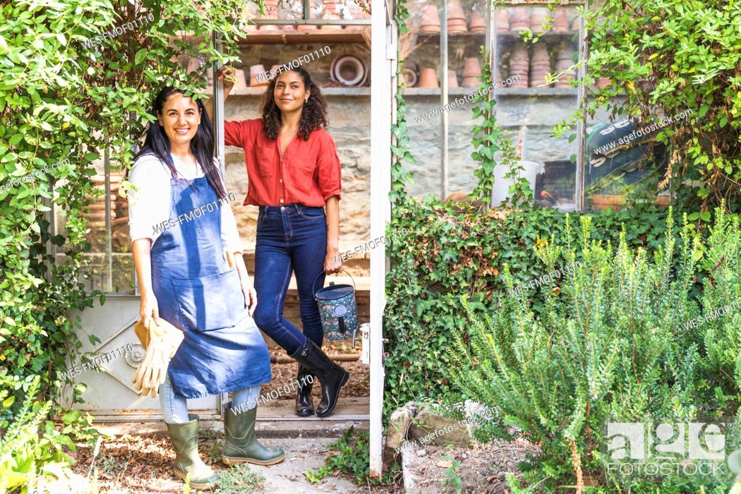 Imagen: Friends standing in back yard with gardening equipment on sunny day.