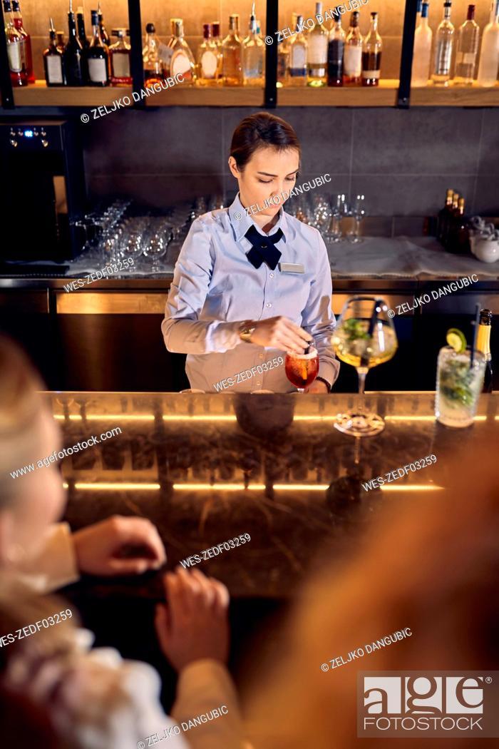 Stock Photo: Barwoman preparing drinks in a bar.