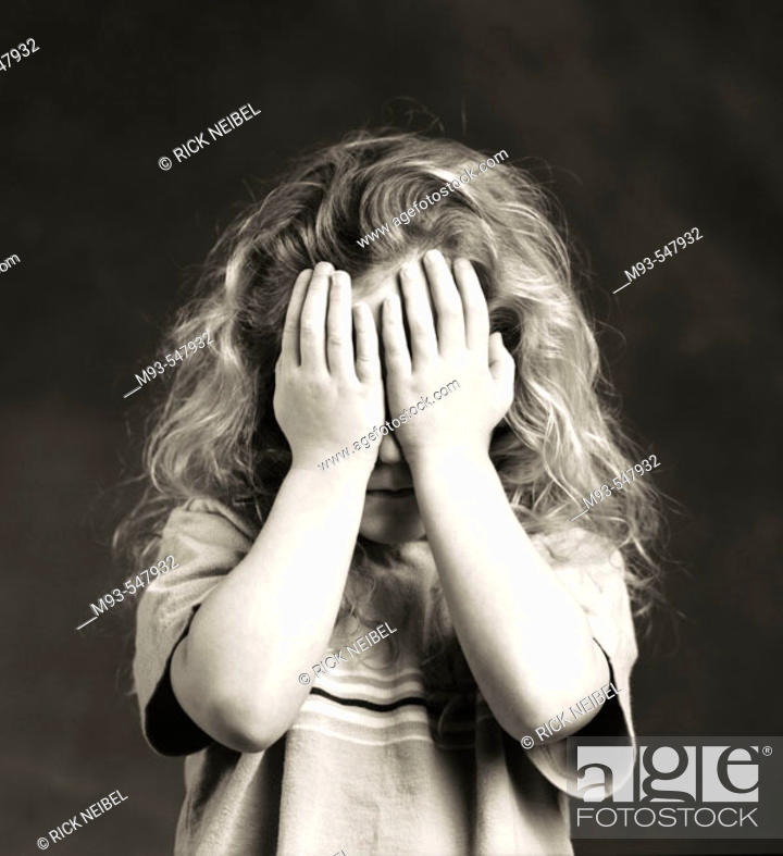 Stock Photo: Black and white of young Caucasian girl approx. 6 years hold holding hands up to her face to cover her eyes.