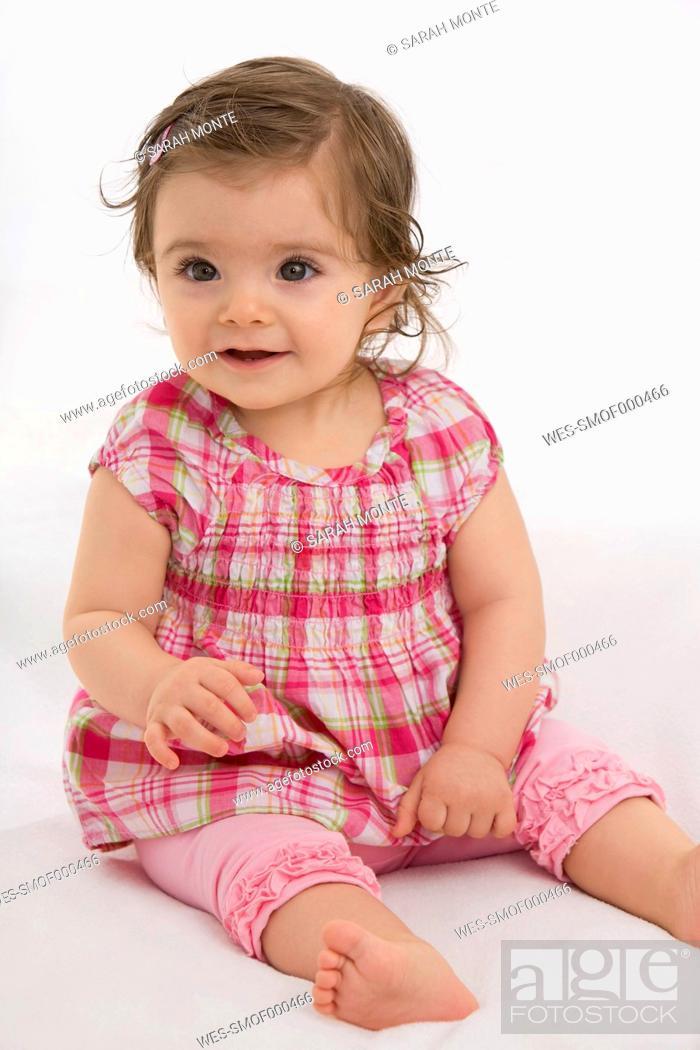 Stock Photo: Baby girl sitting on baby blanket, smiling.
