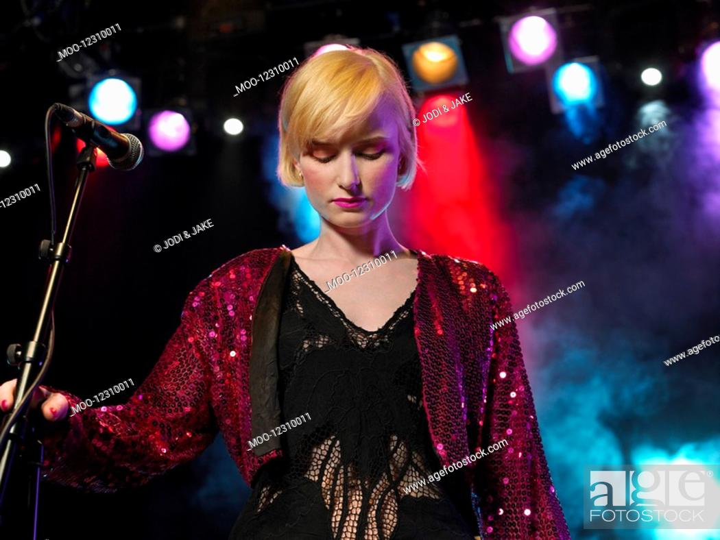 Stock Photo: Young Woman Singing in Concert on stage front view low angle view.