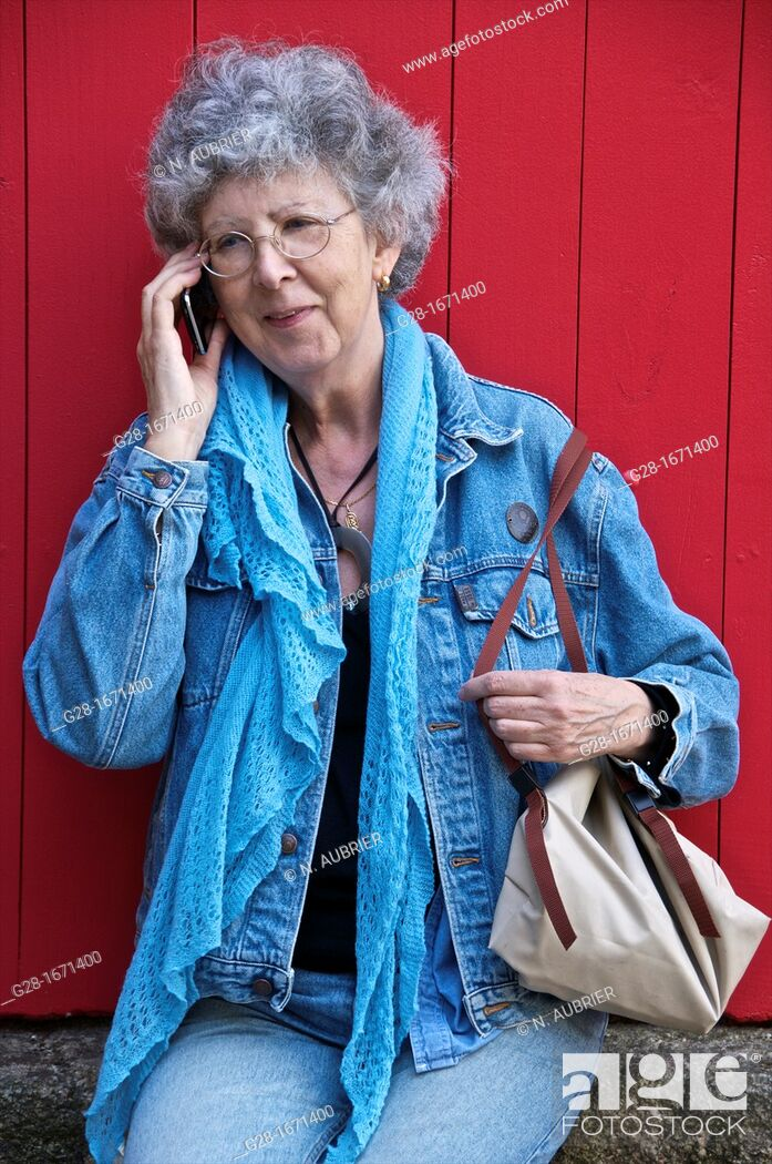 Stock Photo: Senior woman in jeans and blue jeans jacket with woolen scarf, sitting and phoning with a smile.