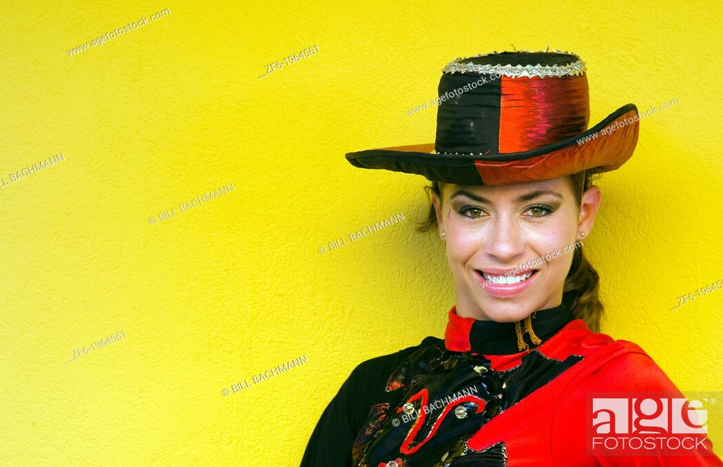 Stock Photo: Trinidad Cuba dancer in costume and hat against yellow wall and smile.
