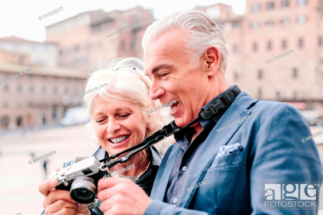 Stock Photo: Tourist couple reviewing digital camera in town square, Siena, Tuscany, Italy.