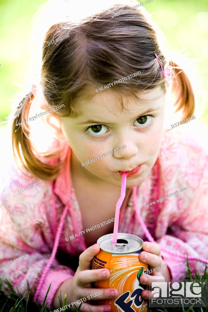 Imagen: Little girl drinking soda with a straw.