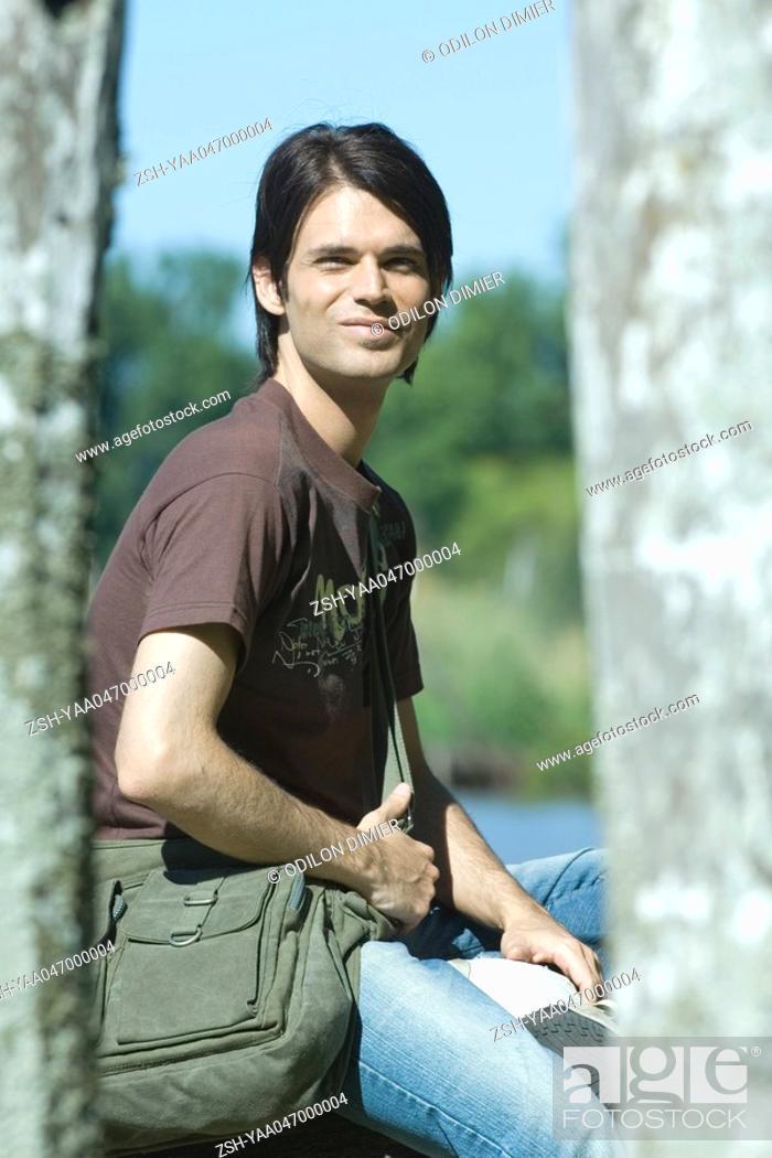 Stock Photo: Man sitting outdoors wearing messenger bag.