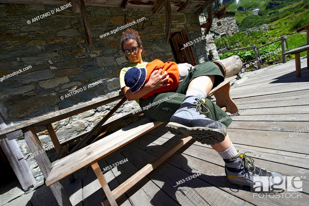 Stock Photo: Mother breastfeeding her six months old baby girl outside a mountain chalet  Alpe Campo  Pennine Alps  Province of Vercelli  Piemonte  Italy.