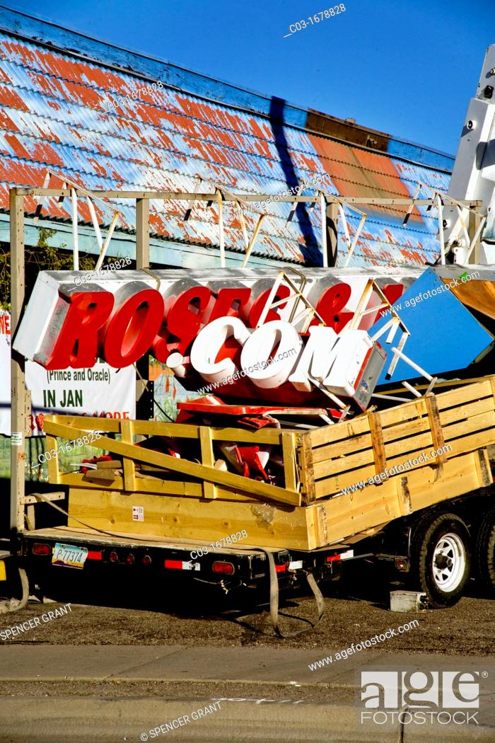 Stock Photo: Workmen remove the sign of an unsuccessful dot-com storefront business in Tucson, AZ.