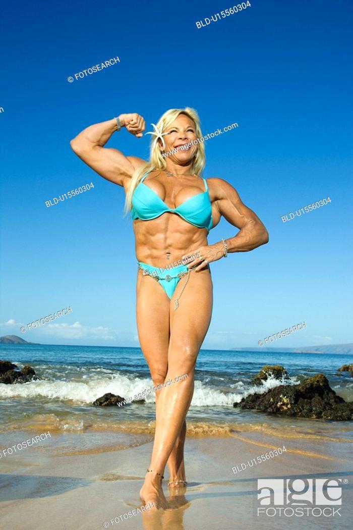 Stock Photo: Pretty Caucasian mid adult woman bodybuilder in bikini flexing bicep on beach.