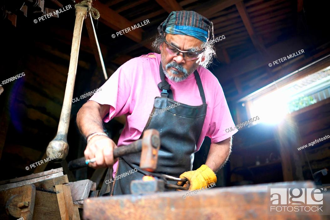 Stock Photo: Blacksmith working in his forge.