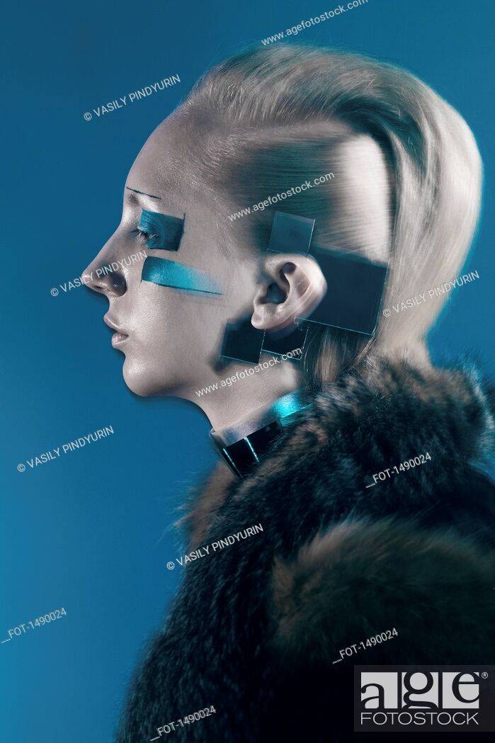 Stock Photo: Side view of confident fashion model in fur coat against blue background.