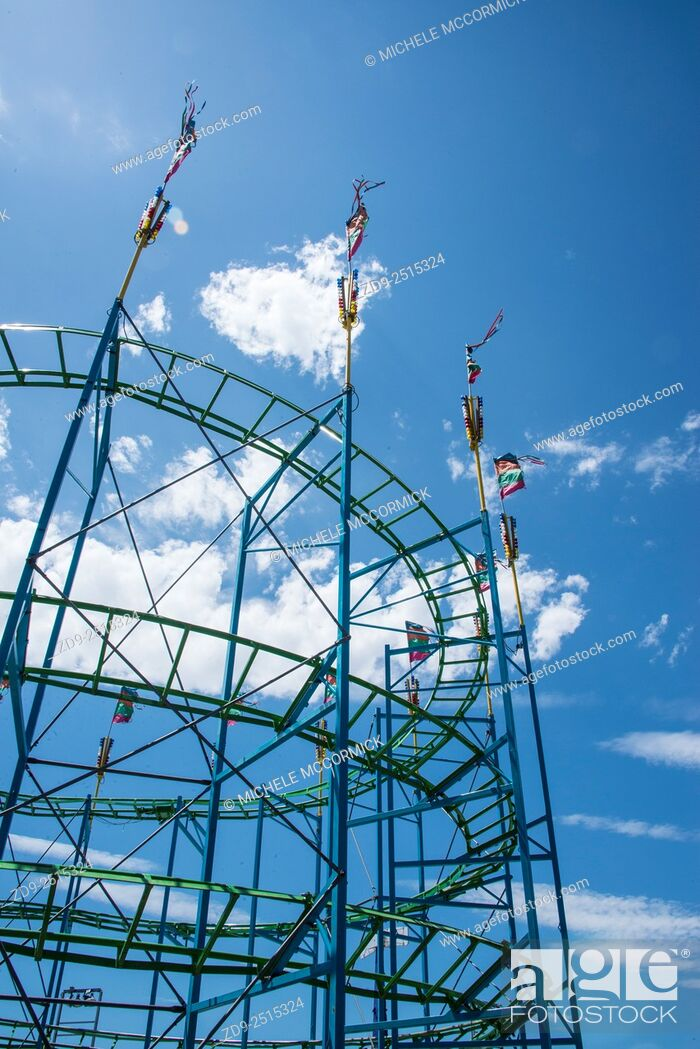 Stock Photo: A carnival roller coaster against a blue sky.