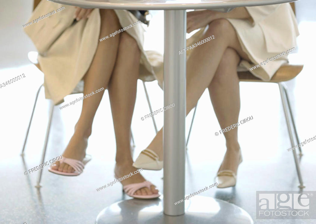 Stock Photo: Two women sitting at table, view of legs under table.