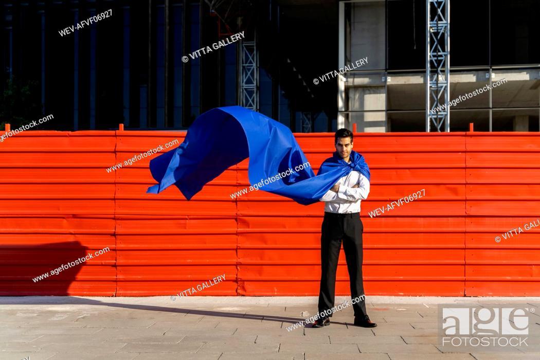 Stock Photo: Confident businessman wearing superhero cape in the city.