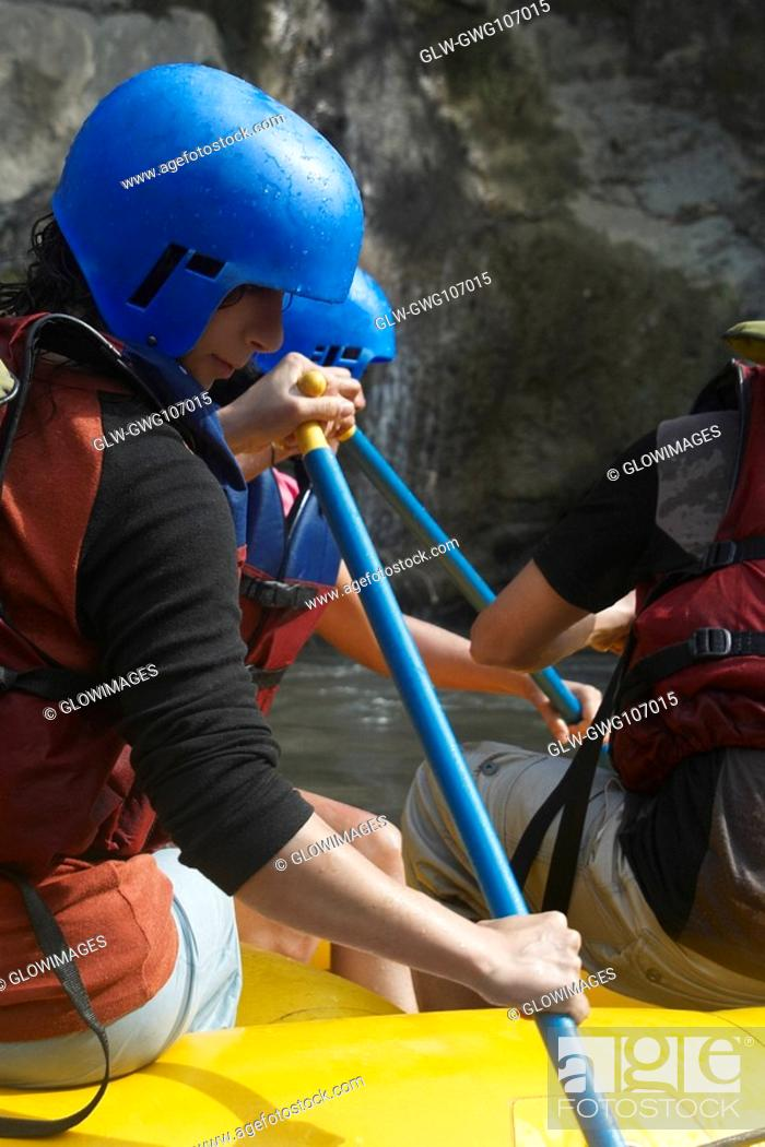 Stock Photo: Three people rafting in a river.