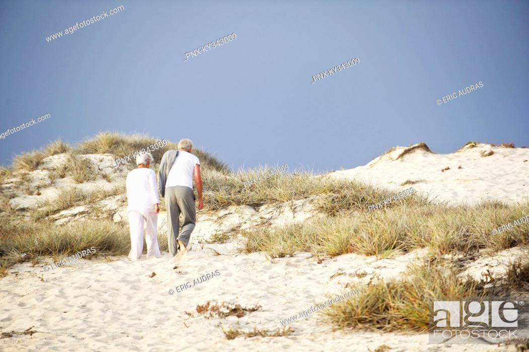 Stock Photo: Rear view of a senior couple walking on the beach.