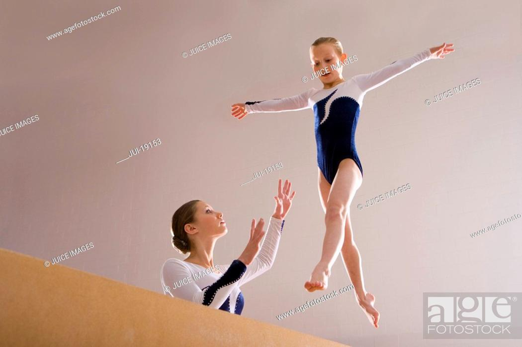 Stock Photo: Gymnastics instructor teaching girl 5-7 on balance beam, low angle view.