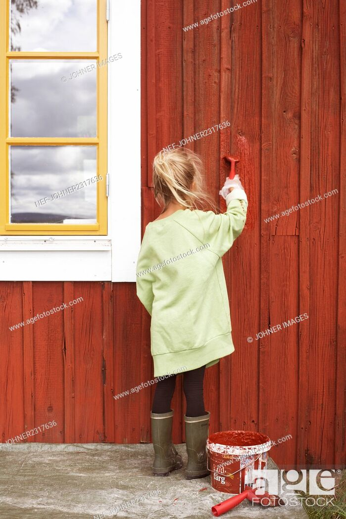 Stock Photo: Girl painting wooden house.