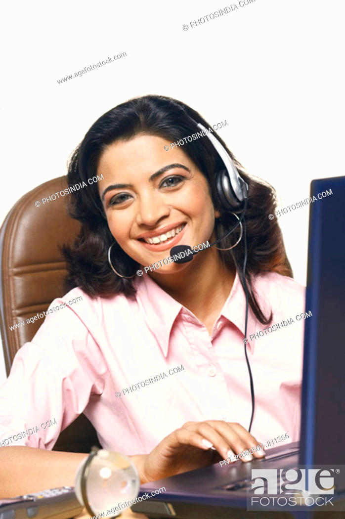 Stock Photo: Portrait of a businesswoman wearing a headset and smiling in front of a laptop.