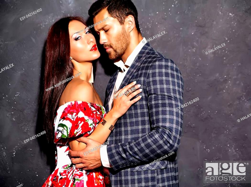 Photo de stock: Fashion photo of handsome elegant man in suit with beautiful sexy woman posing near gray wall.