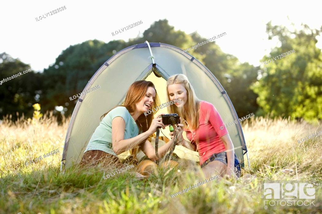 Stock Photo: Two young women sitting in a front of a tent, looking at a camera.