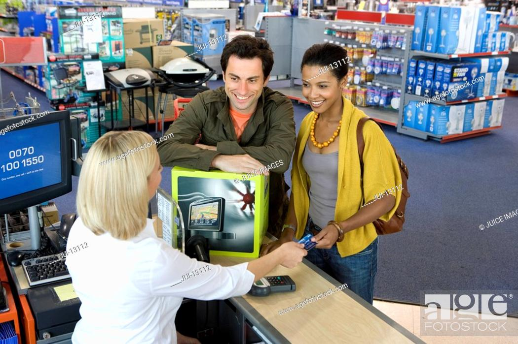 Stock Photo: Young couple buying computer, smiling, elevated view.