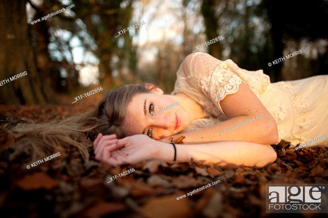 Stock Photo: a slim blonde woman girl alone in woodland autumn afternoon daytime UK.