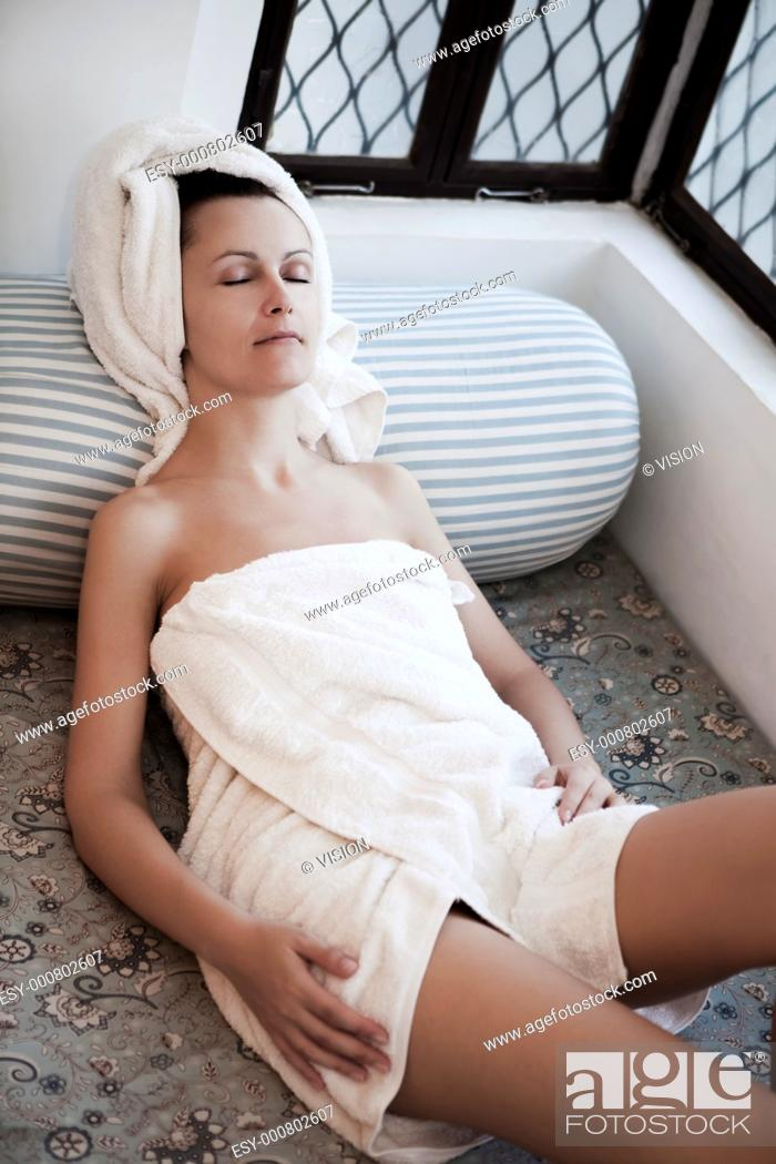 Stock Photo: woman relaxing in a spa lounge in india arabic style applying skincare lotion.