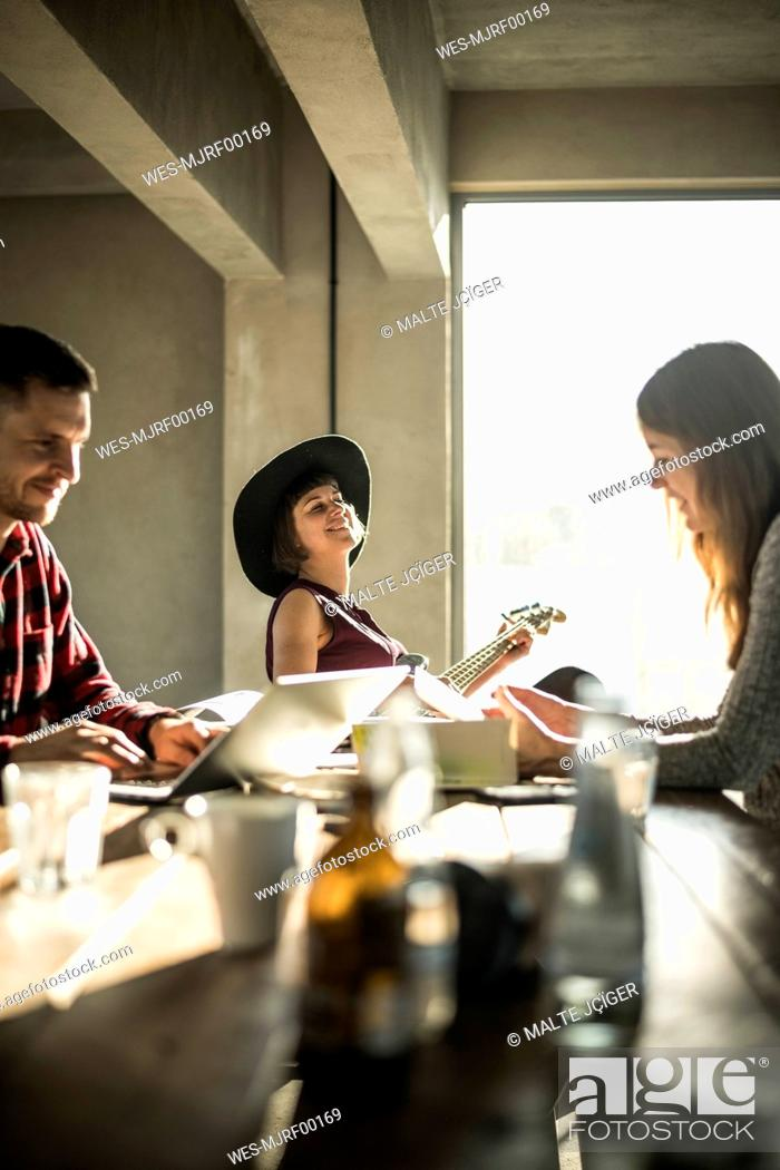 Imagen: Creative professionals working toghether in oficem, woman with hat paying the guitar.