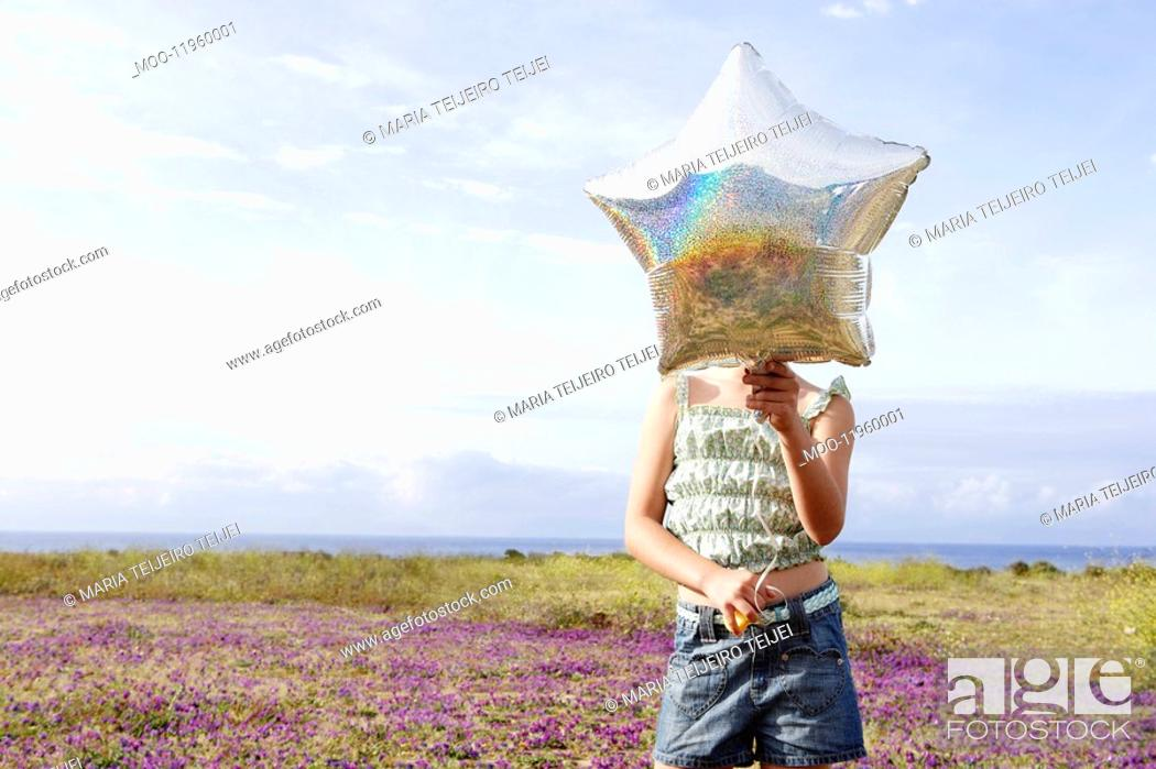 Stock Photo: Little Girl Holding a Balloon in front of face in field of flowers.