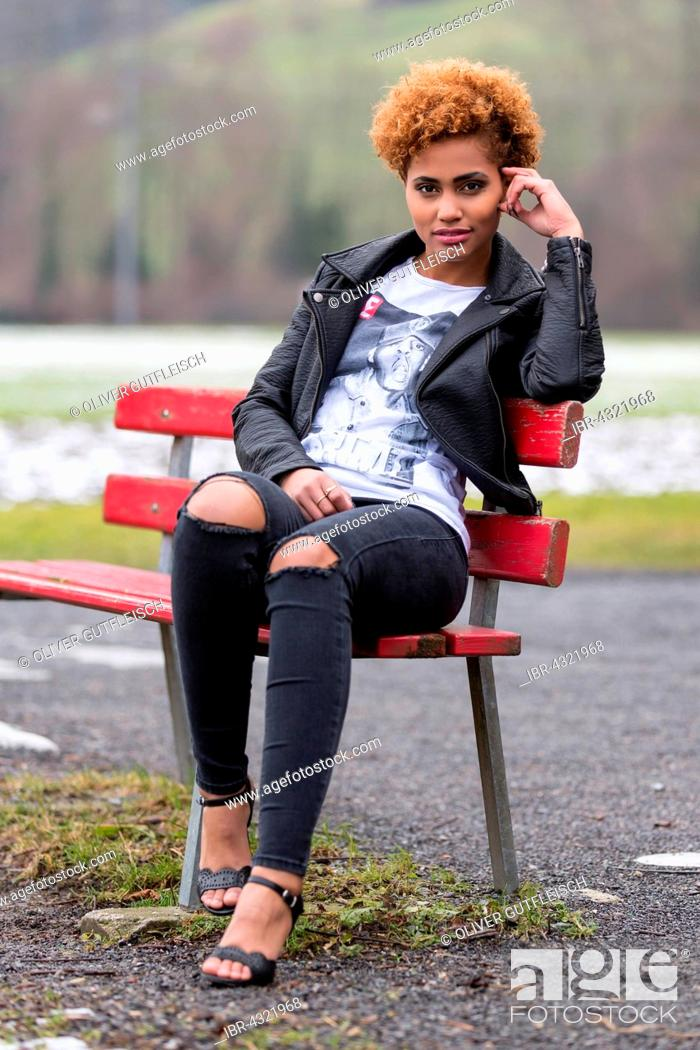 Stock Photo: Young dark woman sitting on a bench, fashion.