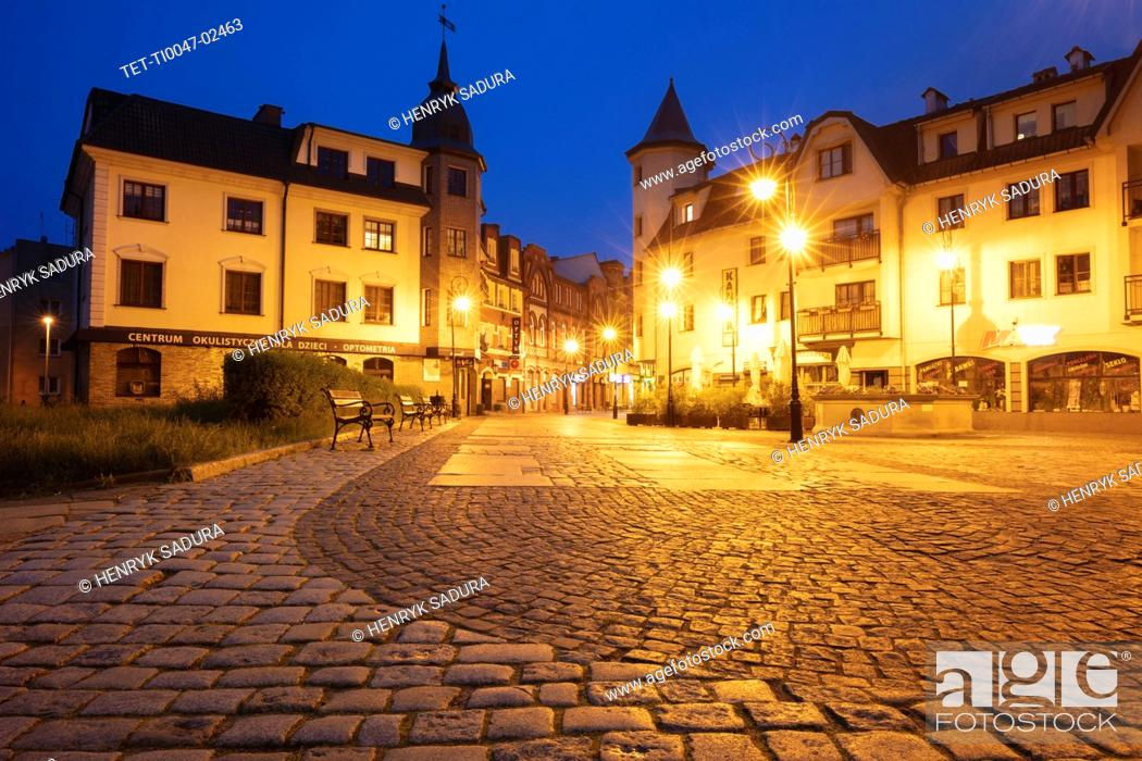 Stock Photo: Poland, Pomerania, Lebork, Illuminated town square at night.